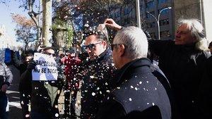 Eduardo Martin responsable de Unauto asociacion de vehiculos con conductor aguanta pacientemente la lluvia de confetis que le lanzan los taxistas en Barcelona.