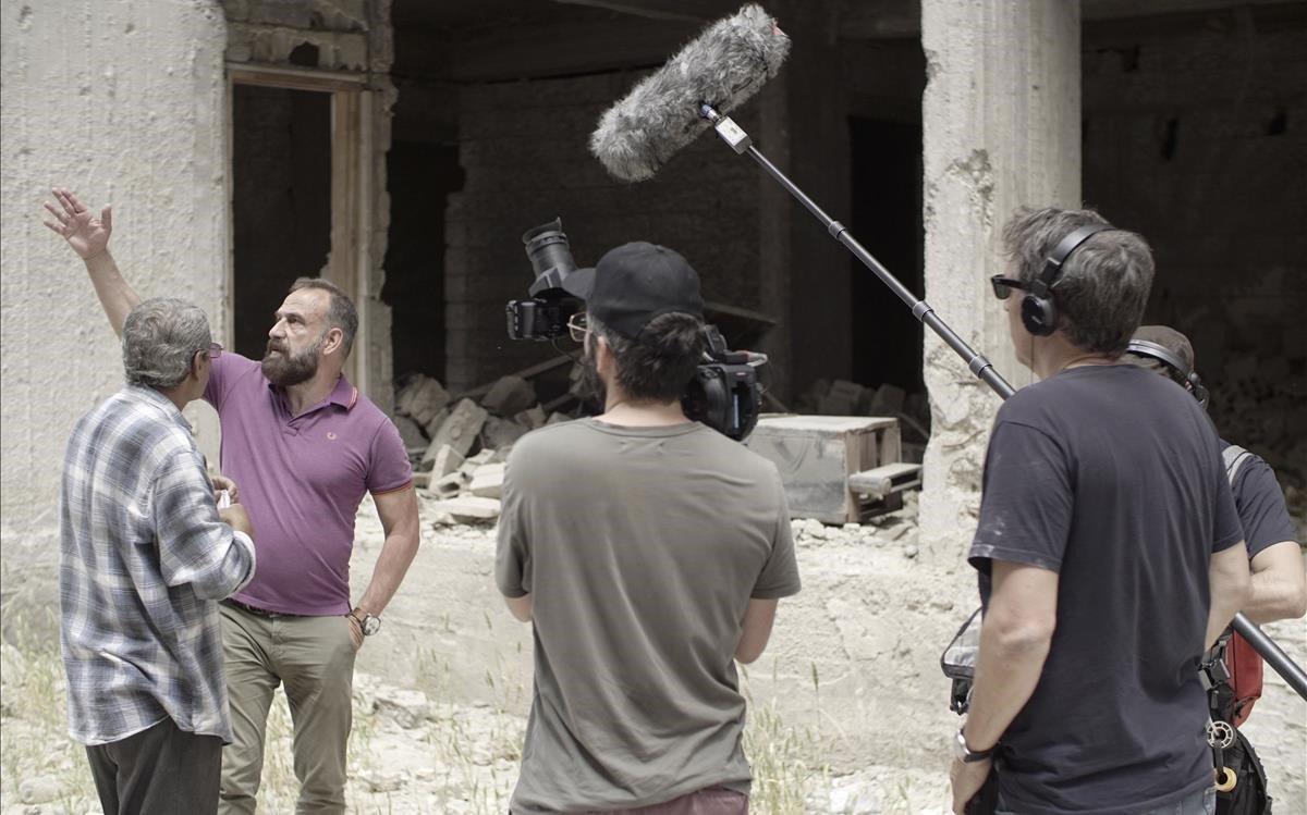 Marc Marginedas conversa con Yunes, uno de los damnificados por los bombardeos, junto al equipo de filmación del documental.