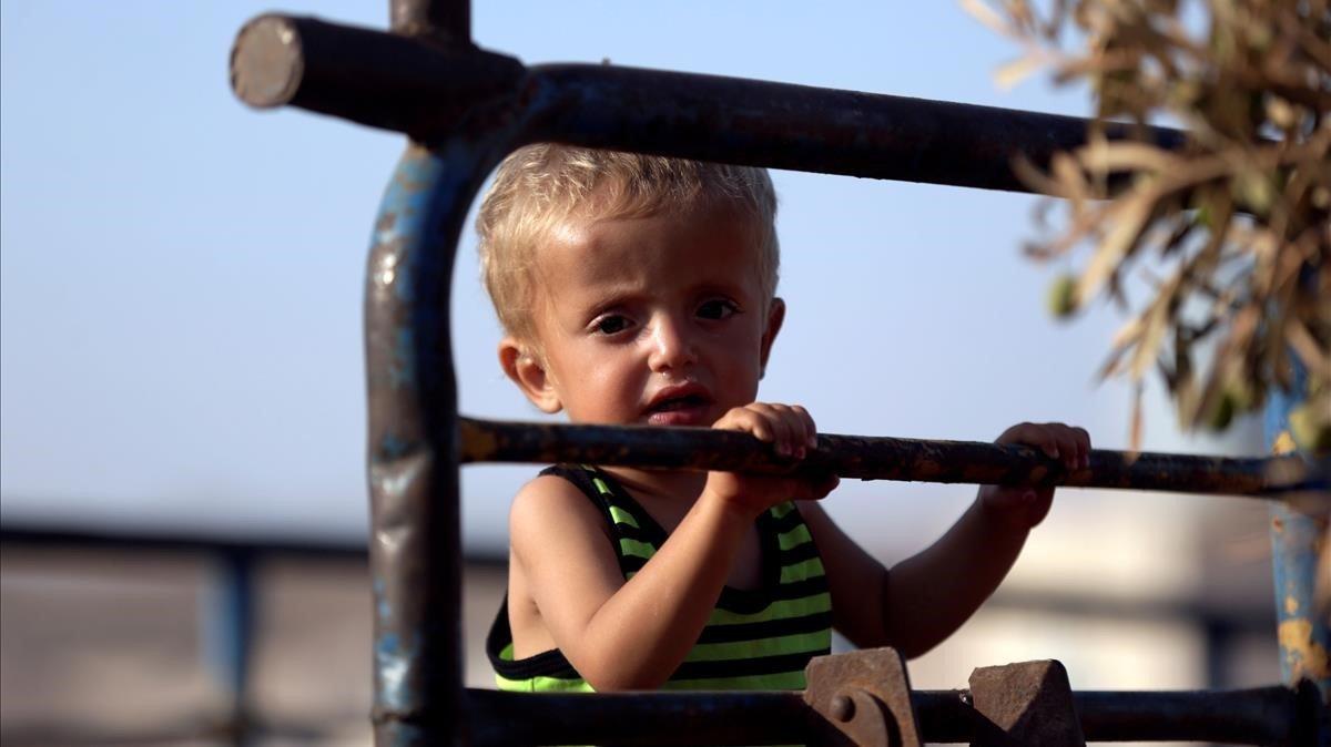 Un niño sirio llega con su familia al campo de refugiados de Idleb, en Siria.