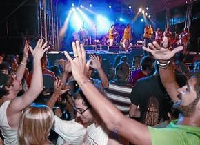Público en la plaza del Sol, coreando una actuación, en unas fiestas de Gràcia.