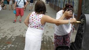 Dos mujeres se refrescan en Barcelona durante la pasada ola de calor.