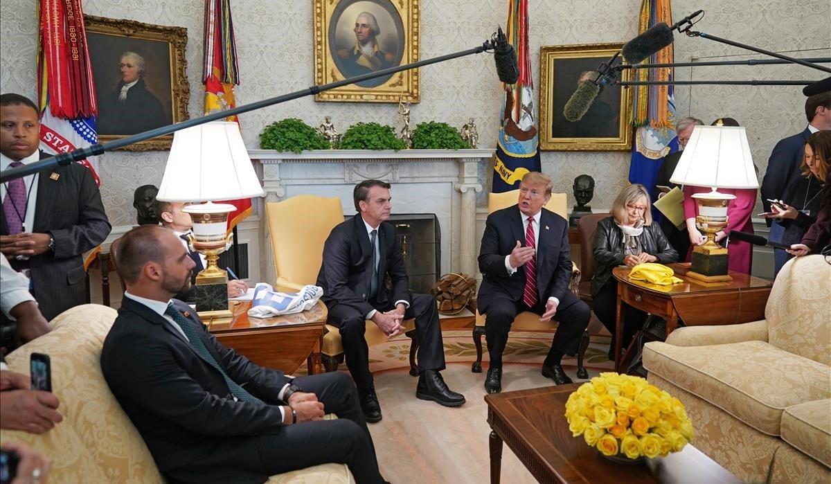 El presidente Donald J Trump se reúne con el presidente brasileño Jair Bolsonaro (centro)acompañado por su hijo Eduardo Bolsonaro (izquierda) en la Casa Blanca de Washington