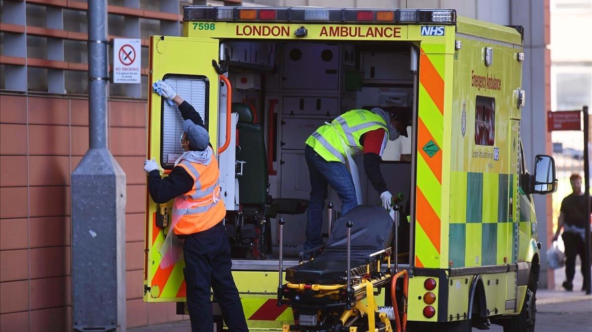 Un equipo de sanitarios desinfecta una ambulancia en el Royal London Hospital de Londres.