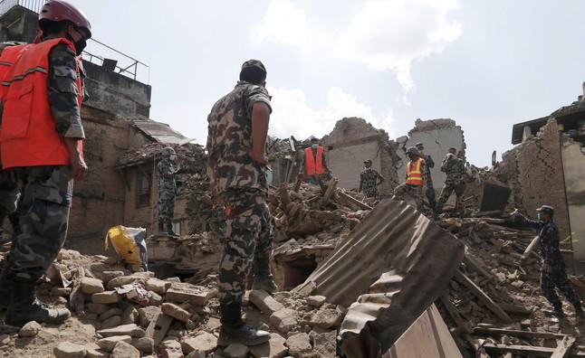 Soldados y equipos de rescate nepalís buscan supervivientes entre los escombros de los edificios caídos tras el terremoto.