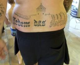 Fotografía facilitada del tatuaje del condenadoque reza Jedem das Seine ( lit. a cada uno lo suyo) bajo lo que parece el campo de exterminio de Auschwitz.