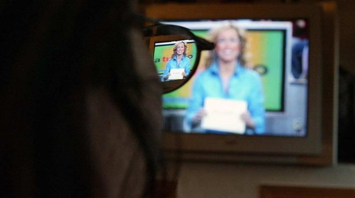 Imagen de un telespectador maduro viendo un programa de televisión en su hogar.