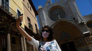 Una mujer con mascarilla se hace un selfi ante la catedral de Tarragona, el 11 de mayo.