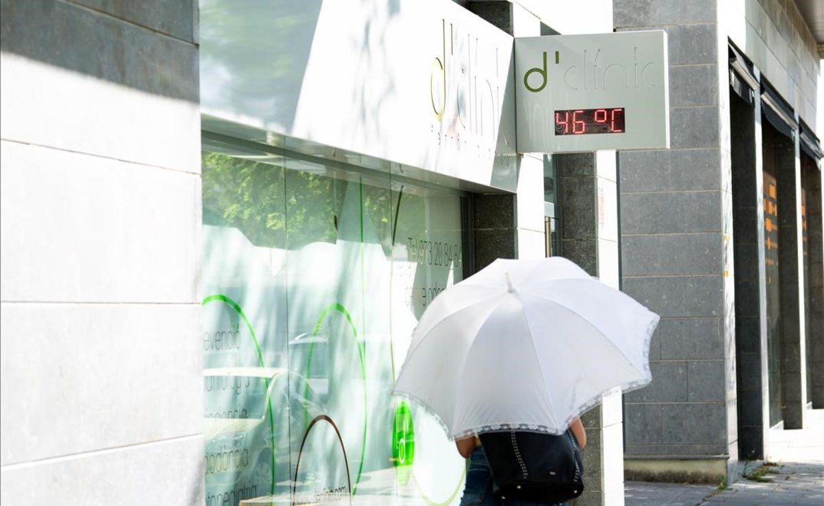 Una mujer pasea protegida por un paraguas en Lleida.