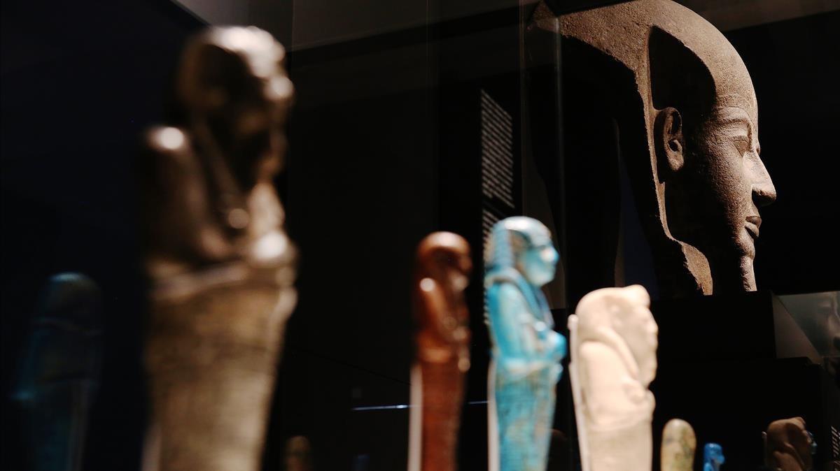 Ushebtis o pequeñas estatuillas que servían al faraón en su tumba, bajo un fragmento de la tapa del sarcófago de Ramsés VI.