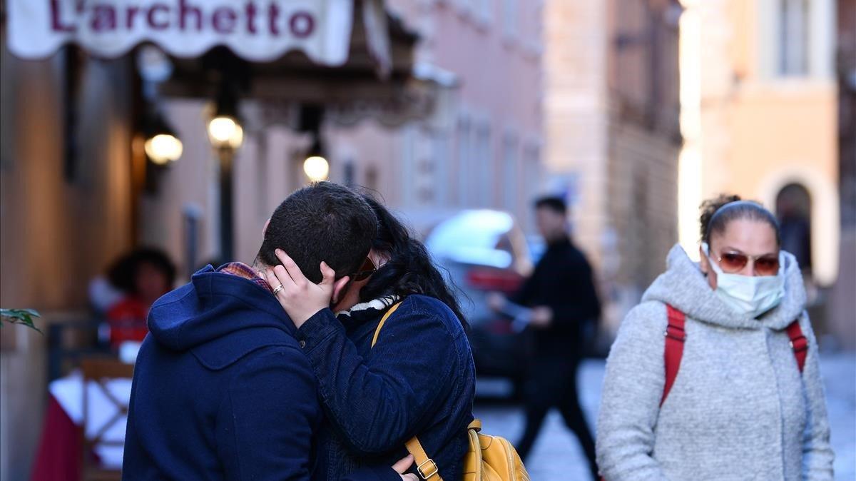 Una mujer con mascarilla observa a una pareja besándose en Roma, este domingo.
