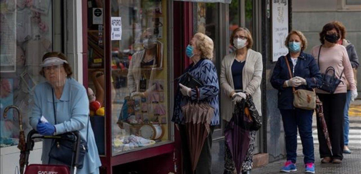 Mujeres hacen cola ante una mercería en el barrio de Triana de Sevilla.