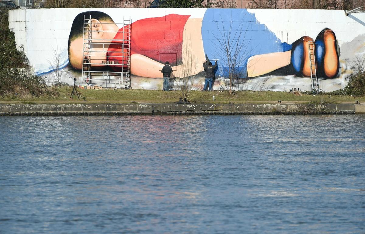 Enorme grafiti de Aylán en la orilla del río que cruza Fráncfort.