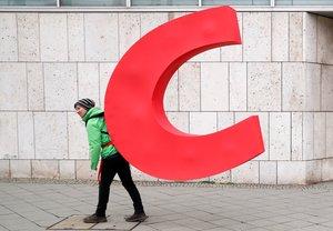 Un activista de Greenpeace se lleva la letra 'C' de la sede de la CDU en Berlín.