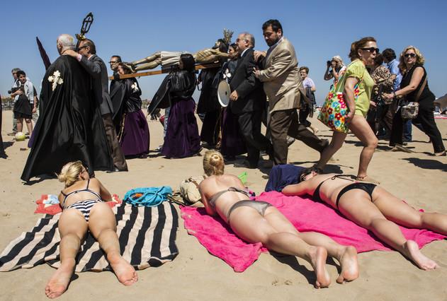 Bañistas y cofrades, en la playa de la Malvarrosa de Valencia, en la Semana Santa del 2014.