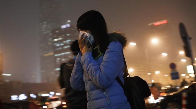 Una mujer se cubre la cara cuando se dirige a una estación de metro de Pekín