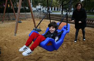 Bruno sonríe mientras su madre le columpia en el parque de la Vila Olímpica.