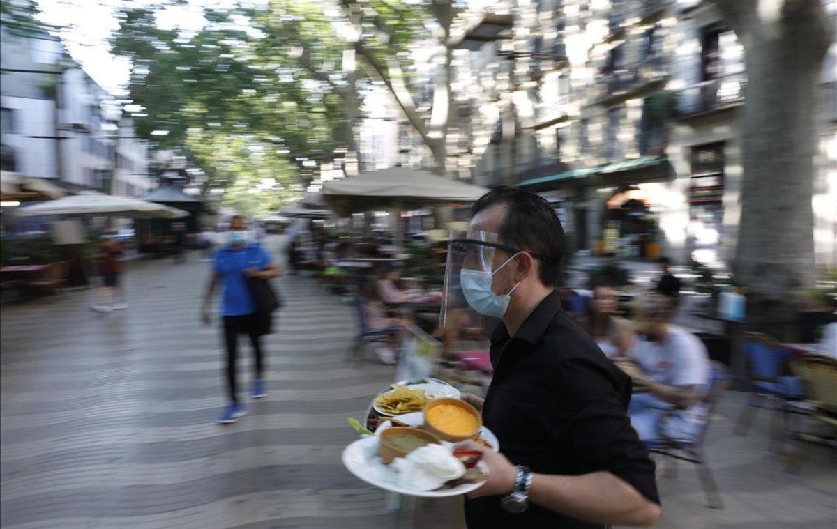Un camarero atiende una terraza en la Rambla.