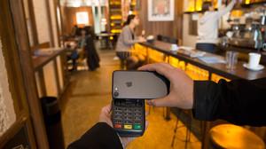 Un cliente paga en un restaurante de Barcelona con su teléfono móvil.