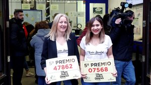 Dos empleadas de la administración de calle Carmen 22, en Madrid, muestran dos quintos premios del sorteo.