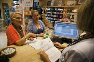 Entrada en vigor del copago sanitario catalán, en una farmacia de Barcelona, el julio pasado.