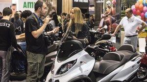 Un especialista comenta las ventajas de una moto de tres ruedas con una visitante de la pasada edición de Vive la Moto.