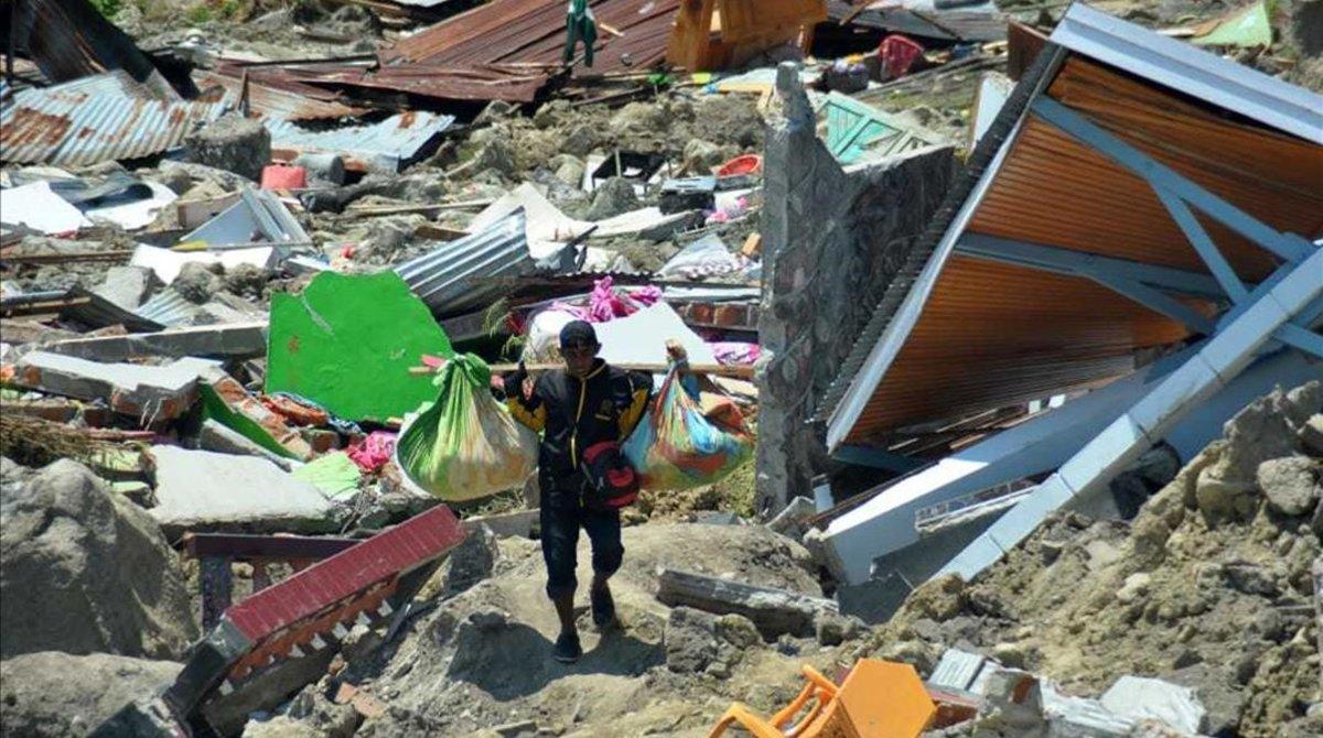 Un hombre carga objetos personales entre los escombros de un edificio derrumbado por el terremoto, en la ciudad indonesia de Palu.