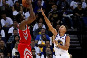 James Harden, de los Rockets, lanza por encima de Curry, estrella de los Warriors