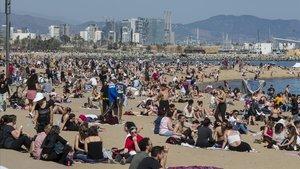 Las altas temperaturas han llenado laplaya de la Barceloneta, este domingo.