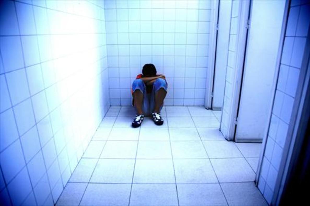 Un joven, víctima de acoso escolar, se refugia en un lavabo.