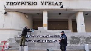 Manifestantes levantan un muro en la sede del Ministerio de Sanidad de Grecia con la inscripción Cerrado por el rescate. Hemos sido trasladados a Bruselas, en una protesta contra la austeridad en Atenas, en diciembre del 2016.