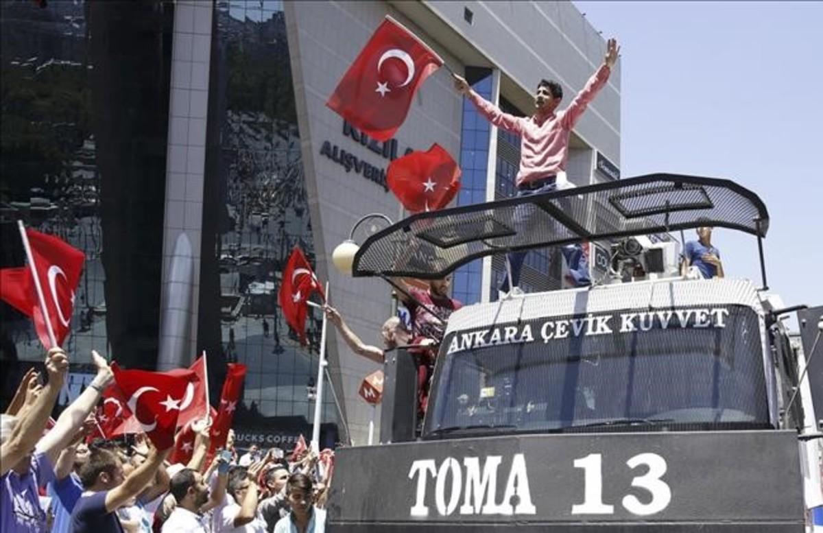 Partidarios de Erdogan celebran el fracaso del golpe, sobre un vehiculo policial en Ankara