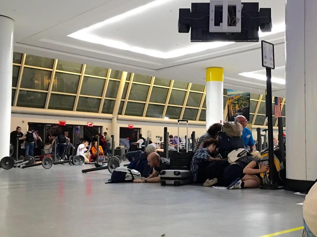 Pasajeros del aeropuerto JFK de Nueva York se protegen mientras la policía busca a unpresunto tirador, la pasada madrugada.