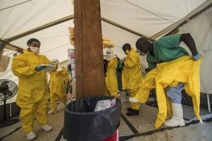 Personal de Médicos sin Fronteras se pone trajes protectores, en un centro sanitario de Kailahun, en Sierra Leona.