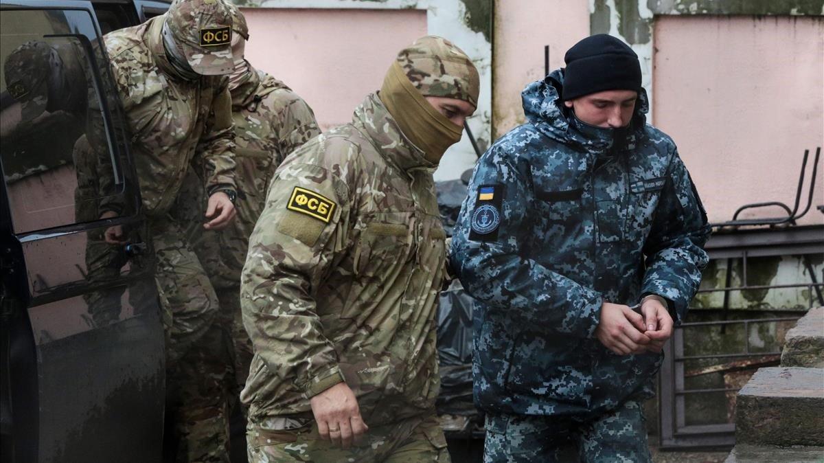 Un policía ruso lleva detenido a un marinero ucraniano en Semforopol.
