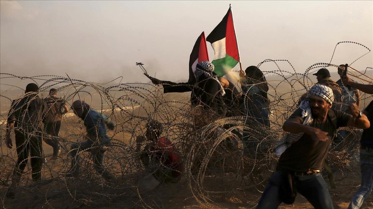 Manifestantes palestinos lanzan piedras contra los soldados israelís en las protestas de este viernes en Khan Younis, en el sur de la frontera de Gaza.
