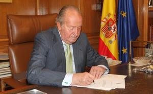 El Rey firma el documento de su abdicación, este lunes.