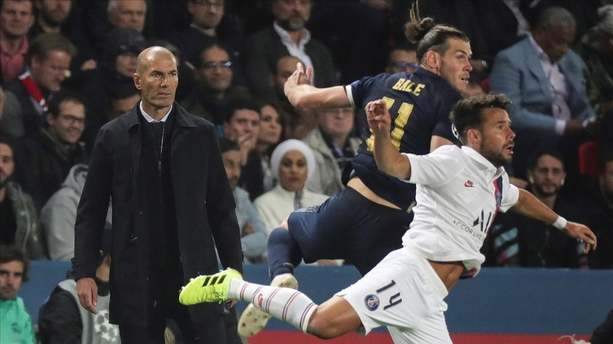 Zidane (derecha) mira una acción del partido entre el Madrid y el PSG protagonizada por Bale y Bernat.