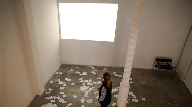 La sala en la que debía proyectarse el video de Nassouh Zaghloulehcon la pared en blanco y las octavillas en el suelo.