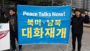 Manifestantes surcoreanos sostienen una pancarta que exige negociaciones de paz con Corea del Norte durante una protesta en Seúl.
