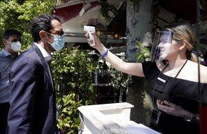 Apertura de terrazas en Madrid que hoy pasa a la fase 1 de la pandemia del covid-19en la imagen una trabajadora de una terraza en Madrid toma la temperatura a los clientes antesde acceder a la terraza.