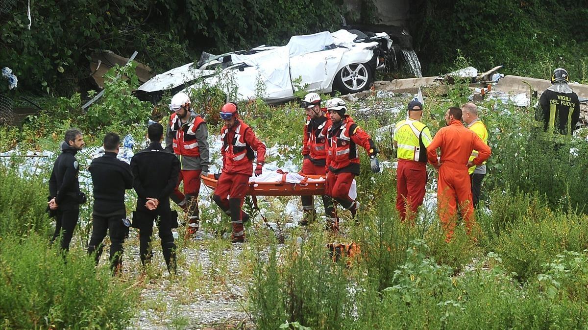 Trabajadores de emergencias trasladan un cuerpo en las ruinas del puente de Génova.
