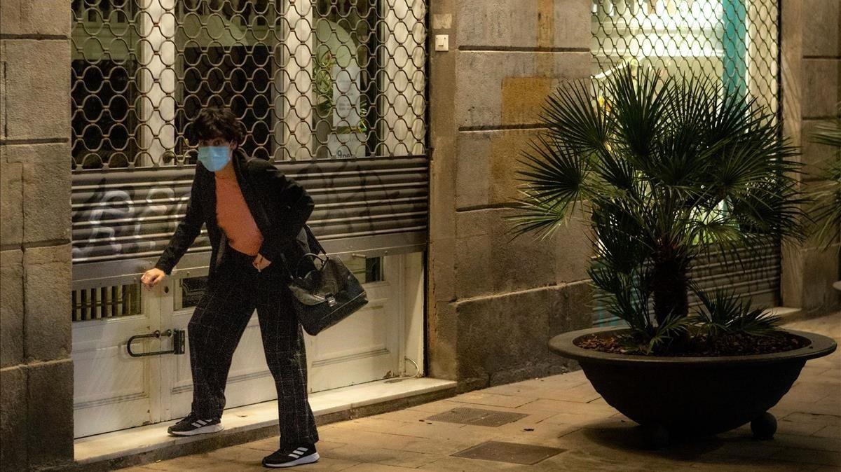 Una mujer con mascarilla echa el cierre a su negocio, el pasado 27 de octubre,en Barcelona.