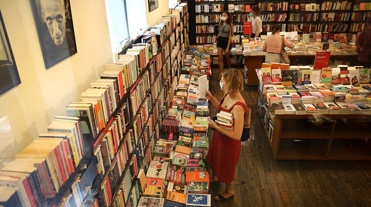 Una mujer lee la contraportada de un libro, en La Central, el pasado 23 de julio, día del llamado Sant Jordi de verano.