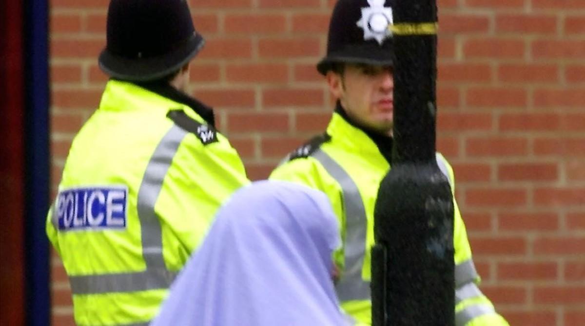 Una mujer musulmana pasa junto a dos policías británicos.