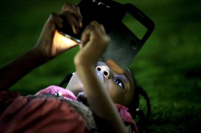 Una niña usa su teléfono móvil en Jartum, la capital de Sudán.