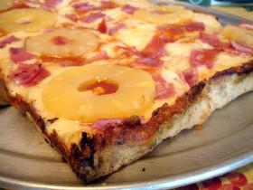 Una porción de pizza hawaiana, con rodajas de piña enteras.
