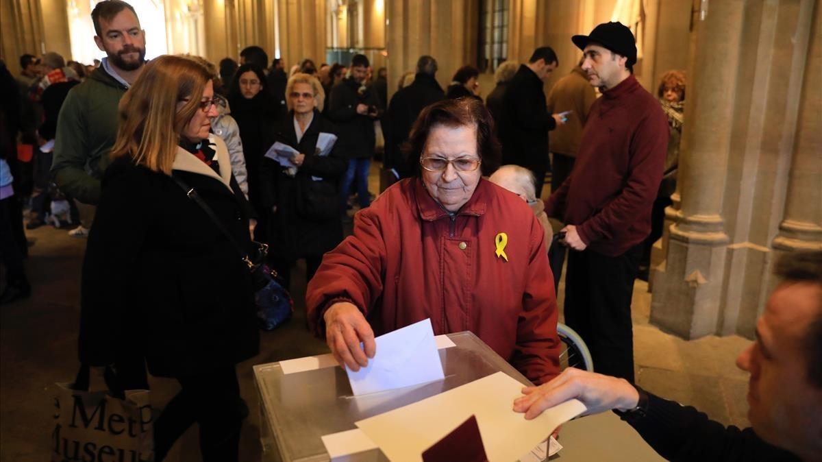 Una señora ejerce su derecho a voto con un lazo amarillo en la solapa.