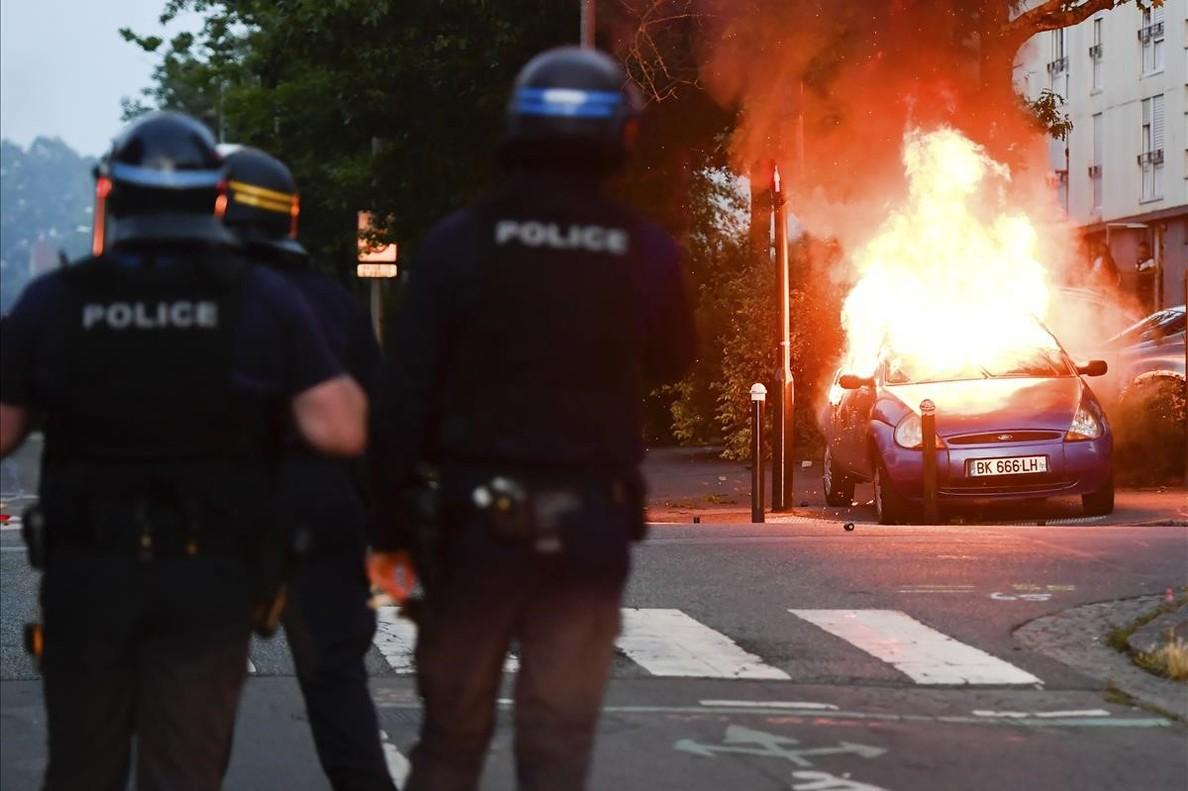 Varios policías ante un coche ardiendo, en Nantes.