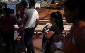 Una madre en Venezuela carga a su hijo con signos de desnutrición.