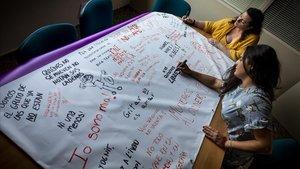 La violencia de género ha aumentado durante los meses de confinamiento.Carla y Xelo de la Asociación Alanna repasan una pancarta.